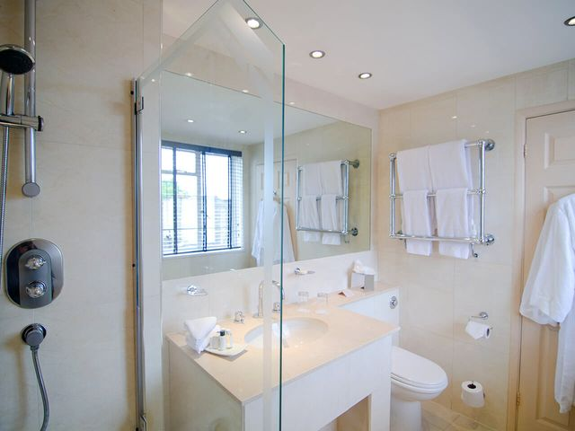 Bathroom with shower, sink and robe in the Beaufort Hotel