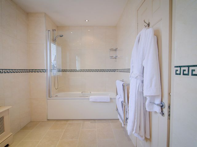 Spacious bathroom with bath, shower and white robe in the Beaufort Hotel