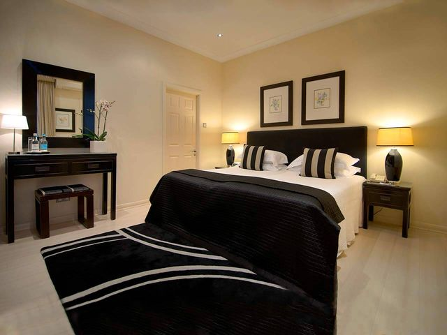 Deluxe Room with fire place, large black rug and large double bed in the Beaufort Hotel