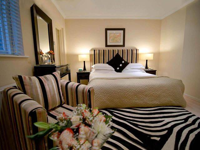 Luxury Deluxe Room with Bed, armchair and zebra print rug in the Beaufort Hotel