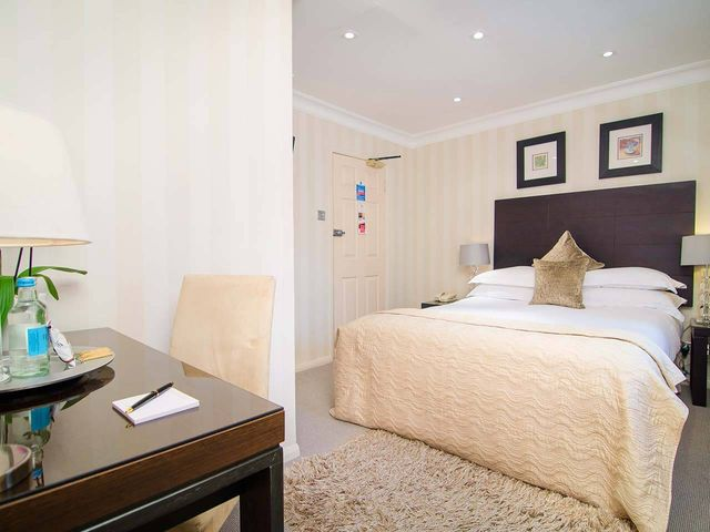 Bright deluxe double room with side table in the Beaufort Hotel