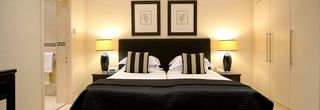 Bed and side tables in Large Deluxe Room in the Beaufort Hotel